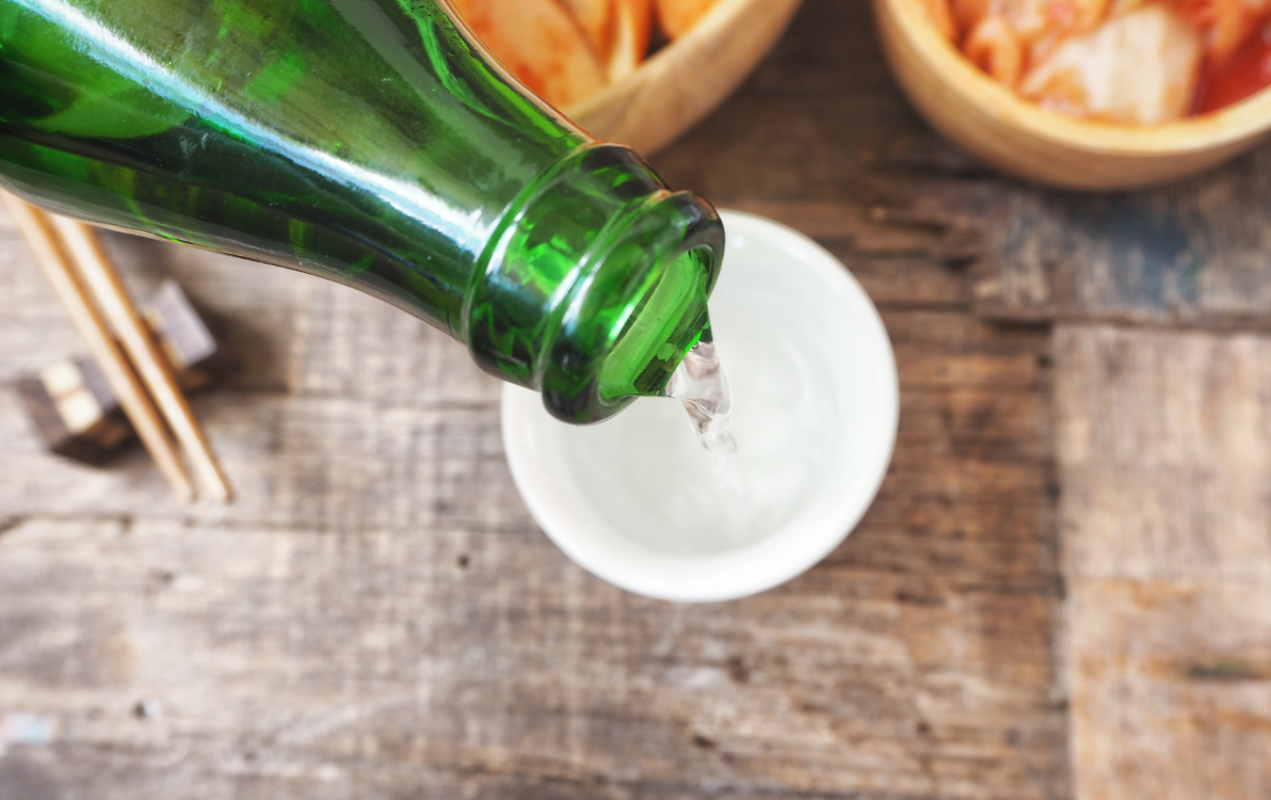 Pouring soju into a white soju glass